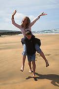Model released girl and boy twins with brother giving her sister a piggy-back ride on the beach, UK