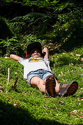 Girl relaxing on moss in forest