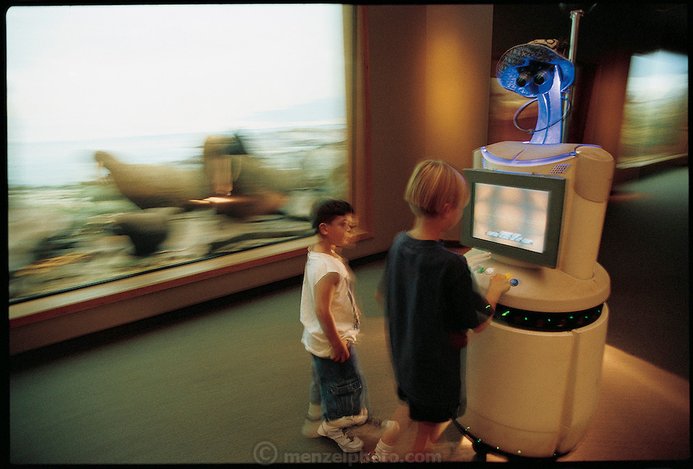 Sweet Lips the robot guide takes visitors through the Hall of North American Wildlife, near the Dinosaur Hall in the Carnegie Museum of Natural History in Pittsburgh, PA. Carnegie Mellon University robotics professor Illah R. Nourbakhsh's creation draws children like a pied piper by speaking and playing informational videos on its screen. It navigates autonomously, using a locator system that detects colored squares mounted high on the wall. A color camera and scores of sonar, infrared, and touch sensors prevent Sweet Lips from crashing into museum displays or museum visitors. From the book Robo sapiens: Evolution of a New Species, page 220-221.