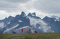 Group of heli-hikers on Rocky Point Ridge. Northern peaks of the Bugaboos in the distance. Bugaboo Provincial Park Purcell Mountains British Columbia.