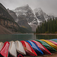 Canoes line a dock beside Moraine Lake below mountains of the Canadian Rockies.