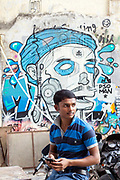 A man uses his mobile telephone in front of graffiti in Hauz Khas Village, New Delhi, India