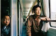 A man and boy aboard a train to Tianshui in China