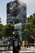 Emergency fire services tackle a blaze at Grenfell Tower near Notting Hill on 14th June 2017 in West London, United Kingdom. The huge fire engulfed the tower block, trapping many people in their homes. A number of fatalities are reported. The block of flats in the Borough of Kensington and Chelsea, billowed large plumes of smoke way above the capital after the blaze broke out in the early hours of Wednesday morning. Londoners came out on the streets to help, offer food and water, support and assistance to those who had lost their homes or didn't know the whereabouts of their friends and family.