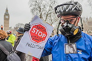 Wearing a mask against pollution and a picture of Karla Roman in remebrance - Stop Killing Cyclists stage a die-in to remember Anita Szucs, 30 and Karla Roman, 32 (both killed while cycling on Monday), and Ben Wales, 32. They are demanding investment in cycling and walking in the hope that it rises to 10% of the UK transport budget by the end of this parliament. They also point out that air pollution is poisoning millions of people in the UK and road danger means most people do not feel safe cycling on UK roads - meaning they miss out on healthy exercise and compounding a health disaster which the NHS will struggle to afford. They met outside the National Gallery and moved to the Treasury, Horse Guards Parade for protest.