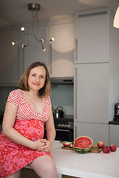 Portrait of a pregnant woman sitting on table in the kitchen and smiling, Munich, Bavaria, Germany