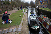 Narrowboat entering a lock on Regents Canal in East London, UK. Regent's Canal crosses an area just north of central London. It provides a link from the Paddington Arm of the Grand Union Canal in the west, to Limehouse and the River Thames in east London. The canal is 13.8 kilometres (8.6 miles) long.