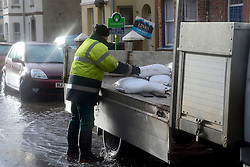 © Licensed to London News Pictures. 03/02/2014. Exmouth, UK . A worker delivers sandbags. Seawater floods the seafront in Exmouth Devon.The water breached defences and flooded Morton Road, St Andrews Roads, Victoria Road and some of the other surrounding streets. Police closed the road to vehicles. Officials were seen delivering sandbags to the local residents. . Photo credit : Russ Nolan/LNP