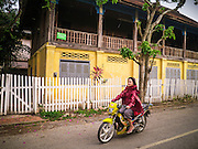 11 MARCH 2013 - LUANG PRABANG, LAOS: A woman rides her scooter past a colonial era shophouse in Luang Prabang, Laos. Luang Prabang is a UNESCO World Heritate Site and building renovations have to be done in a historically accurate way.     PHOTO BY JACK KURTZ