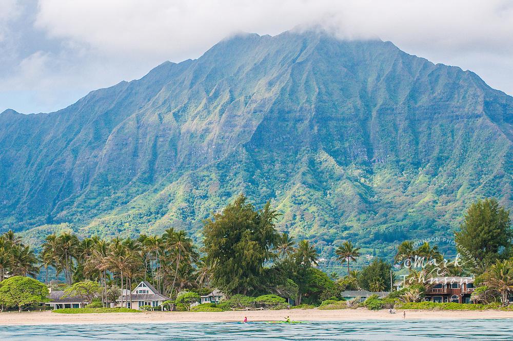 Couple paddling single-man outrigger canoes in the foreground off of Kailua Beach, with Mt. Konahuanui, highest peak of the Koolau Mountain Range in the background, Kailua, Oahu, Hawaii