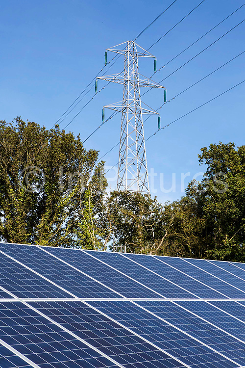 An electricity pylon towering over the solar panels of the 100kW solar array built by WREN, in partnership with South West Water, to power Nanstallon Sewage Treatment Works. WREN community energy. Wadebridge, Cornwall. UK