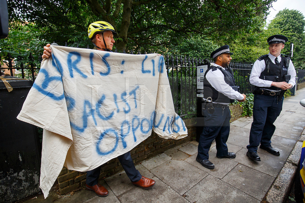 """© Licensed to London News Pictures. 30/06/2016. London, UK. A protester with a banner reads """"BORIS: LIAR, RACIST, OPPORTUNIST"""" standing outside former Mayor of London Boris Johnson's house before leaving his house in London ahead of a press conference to make his bid to be next Conservative leader and UK Prime Minister on 30 June 2016. Photo credit: Tolga Akmen/LNP"""