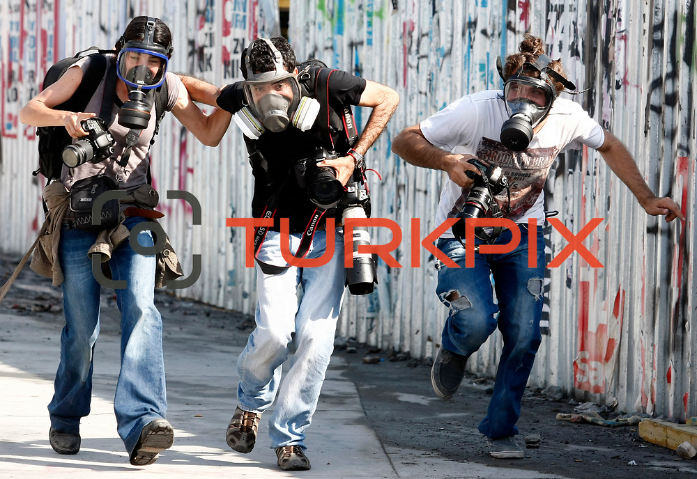 Turkish photographers seen. Turkish police use tear gas to disperse protestors during a clash at Taksim Square in Istanbul, Turkey, 11 June 2013. Turkey's crackdown on opposition protesters reportedly left at least two dead and more than 1,000 injured. Photo by AYKUT AKICI/TURKPIX