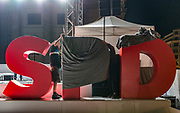 Stage crew members are seen covering the letters of the SPD logo after a Martin Schulz (SPD) campaign event at the Gendarmenmarkt Square in Berlin, on September 22, 2017. Schulz, Chancellor Candidate and Head of the Social Democratic Party was chosen unanimously earlier this year to serve as the party's leader. As an outsider coming directly from a position in the European Parliament Schulz was trusted by his party's leadership to lead it to victory in the 2017 elections, during the first months of his campaign run he managed to keep a tight gap behind The Chancellor Angela Merkel, a gap that went broader and broader as the campaign moved on. General elections will take place in Germany, on September 24, current polls show that Schulz's party falls about 14 percent points behind The Chancellor Angela Merkel's party The Christian Democratic Union (CDU). He is supposed to face growing criticism from his fellow party members as it is predicted that its total vote count will shrink.<br /> (Photo by Omer Messinger)