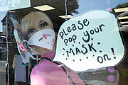 With most shops now open but with retail sales suffering due to the Coronavirus pandemic, a local charity shop asks customers to wear face maks, which became compulsory in shops on the 24th July, go out shopping on Kings Heath High Street on 31st July 2020 in Birmingham, United Kingdom. Coronavirus or Covid-19 is a respiratory illness that has not previously been seen in humans. While much or Europe has been placed into lockdown, the UK government has put in place more stringent rules as part of their long term strategy, and in particular social distancing.