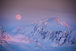 Full moon above Svalbard mountains in Smeerenburgfjorden in March at the northern tip of Spitsbergen, Svalbard, Norway