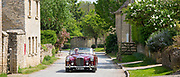 Motorist driving 1961 British made Alvis TD21 drophead ooupe classic car on country lane, Asthall village, The Cotswolds England