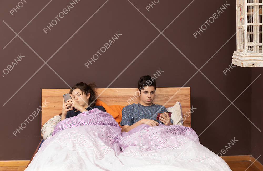 brother and sister in the same bed chatting with phone