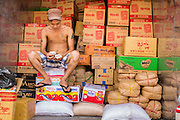 """12 APRIL 2012 - HO CHI MINH CITY, VIETNAM:  A vendor counts his money in his shop (which is the back of a truck) in Binh Tay Market. Binh Tay market is the largest market in Ho Chi Minh City and is the central market of Cholon. Cholon is the Chinese-influenced section of Ho Chi Minh City (former Saigon). It is the largest """"Chinatown"""" in Vietnam. Cholon consists of the western half of District 5 as well as several adjoining neighborhoods in District 6. The Vietnamese name Cholon literally means """"big"""" (lon) """"market"""" (cho). Incorporated in 1879 as a city 11km from central Saigon. By the 1930s, it had expanded to the city limit of Saigon. On April 27, 1931, French colonial authorities merged the two cities to form Saigon-Cholon. In 1956, """"Cholon"""" was dropped from the name and the city became known as Saigon. During the Vietnam War (called the American War by the Vietnamese), soldiers and deserters from the United States Army maintained a thriving black market in Cholon, trading in various American and especially U.S Army-issue items.         PHOTO BY JACK KURTZ"""