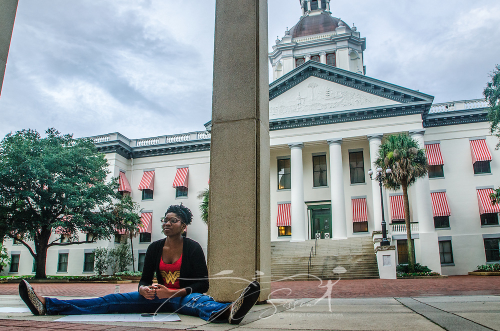 """LaQuinta Alexander, 21, sits outside the Florida state capitol in Tallahassee, Fla., on July 20, 2013, in support of Dream Defenders, a youth-led activist group which sequestered itself within the building July 16, 2013, demanding a special legislative session to address concerns over racial profiling and Florida's """"stand-your-ground"""" self-defense law. The group formed in 2012 after the fatal shooting of 17-year-old Trayvon Martin.  (Photo by Carmen K. Sisson/Cloudybright)"""