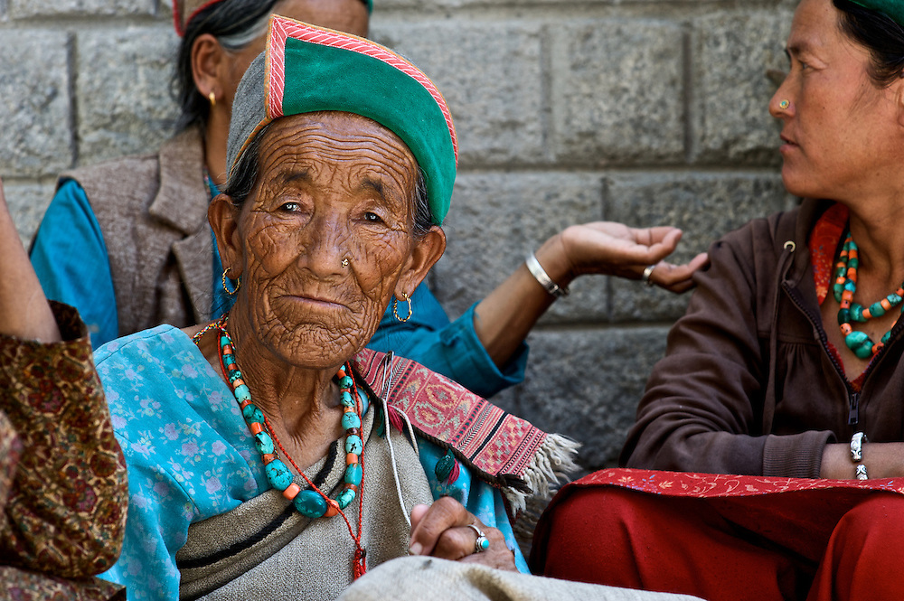 A Kinnauri woman wears her traditional hat and jewelry as she waits outside a medical clinic in the Ropa Valley, Himachal Pradesh, India