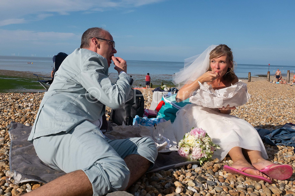 Newlywed groom Paul and bride Zoe have just been married at a nearby beach venue and continue their wedding ceremony by eating bags of chips on the shingle overlooking the Thames Estuary at Whitstable,  on 18th July 2020, in Whitstable, Kent, England. Due to the Coronavirus pandemic restrictions, large social gatherings such as weddings are currently restricted to a maximum of 30 guests and officlas so Paul and Zoes own ceremony was witnessed by just a few family and friends.