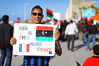A pro-rebel supporter holds up a sign thanking France for its intervention in the no-fly zone over Libya