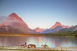 Horseback riders, Swiftcurrent Lake, sunrise, Glacier National Park