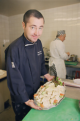 Chef displaying tray of food prepared in hospital kitchen for functions,