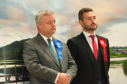 © Licensed to London News Pictures. 01/08/2019. Llanelwedd, Powys, UK.  Chris Davies (L) conservative and Tom Davies Labour listen to Jane Dodds speech. Jane Dodds Liberal Democrats wins the by-election. The Brecon & Radnorshire by-election count takes place in the Food Hall of the Royal Welsh Agricultural Society showground. <br /> The by-election has been recalled because the incumbent Tory MP. Chris Davies, who has been convicted for faking expenses claims, has been booted from the seat after a recall petition was passed when more than 10,000 voters backed the move. <br /> Candidates for the by-election are: Brexit Party - Des Parkinson. Conservative - Christopher Davies. Labour - Tom Davies. Liberal Democrats - Jane Dodds. Monster Raving Loony - Lady Lily the Pink. UKIP - Liz Phillips. Photo credit: Graham M. Lawrence/LNP