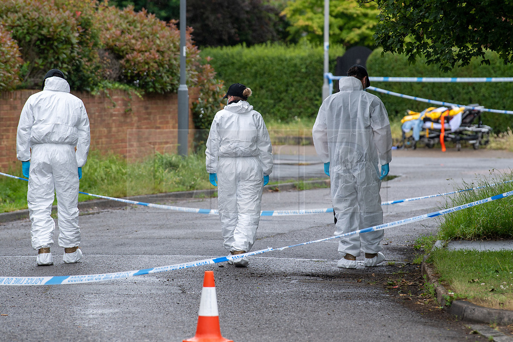 © Licensed to London News Pictures. 21/06/2021. Burnham, UK. Members of a Thames Valley Police search team and an ambulance stretcher in the background at the scene following the death of a man in Wyndham Crescent in Burnham on Monday 20/06/2021. Emergency services were called at approximately 13:10BST to the Buckinghamshire street following reports of an altercation involving a group of men. Shortly after this a 35-year-old man collapsed. Thames Valley Police officers and paramedics attended the scene and performed CPR on the man but he was later pronounced dead. Photo credit: Peter Manning/LNP