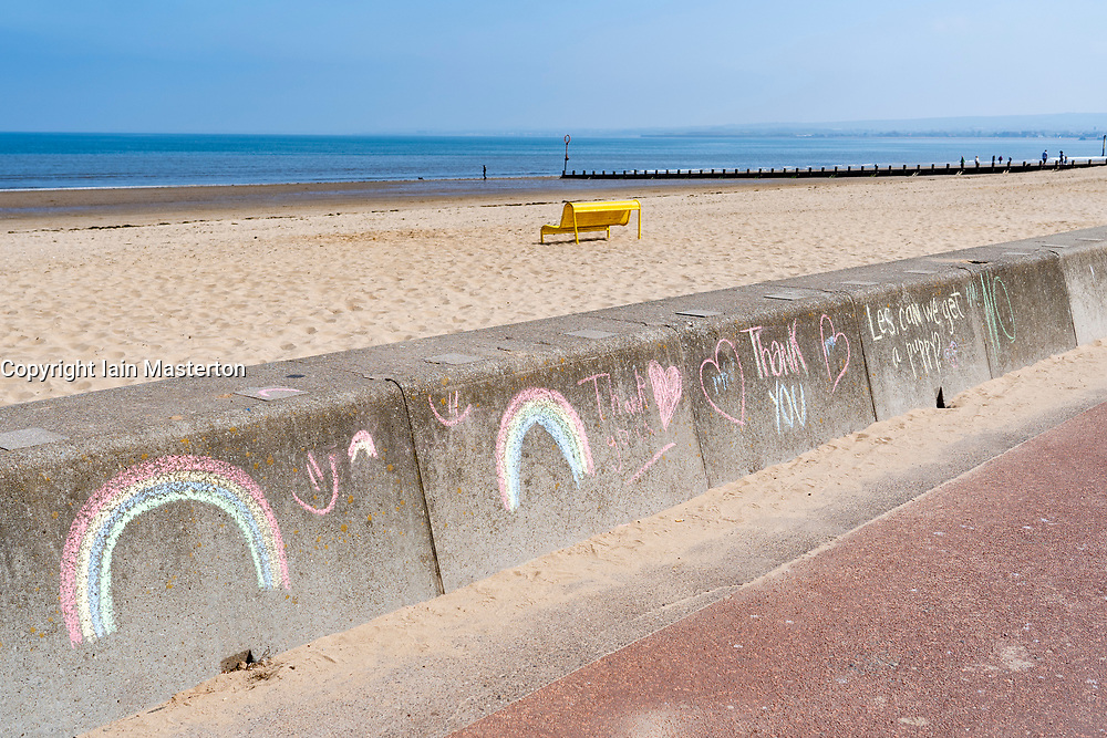 Portobello, Scotland, UK. 25 April 2020. Views of people outdoors on Saturday afternoon on the beach and promenade at Portobello, Edinburgh. Good weather has brought more people outdoors walking and cycling. Police are patrolling in vehicles but not stopping because most people seem to be observing social distancing. Rainbows chalked to seawall with empty beach. Iain Masterton/Alamy Live News