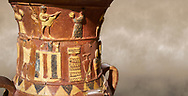 Close up of the Inandik Hittite relief decorated cult libation vase decorated with a women and man relief figures coloured in cream, red and black playing instruments, in the register below is a cult altar, mid to late 16th century BC - İnandıktepe, Turkey. Against a warm art background