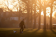 A pet owner kicks a football as his energetic terrier dog chases at his feet in an urban setting sun, on 5th January 2017, in Ruskin Park, London borough of Lambeth, England.