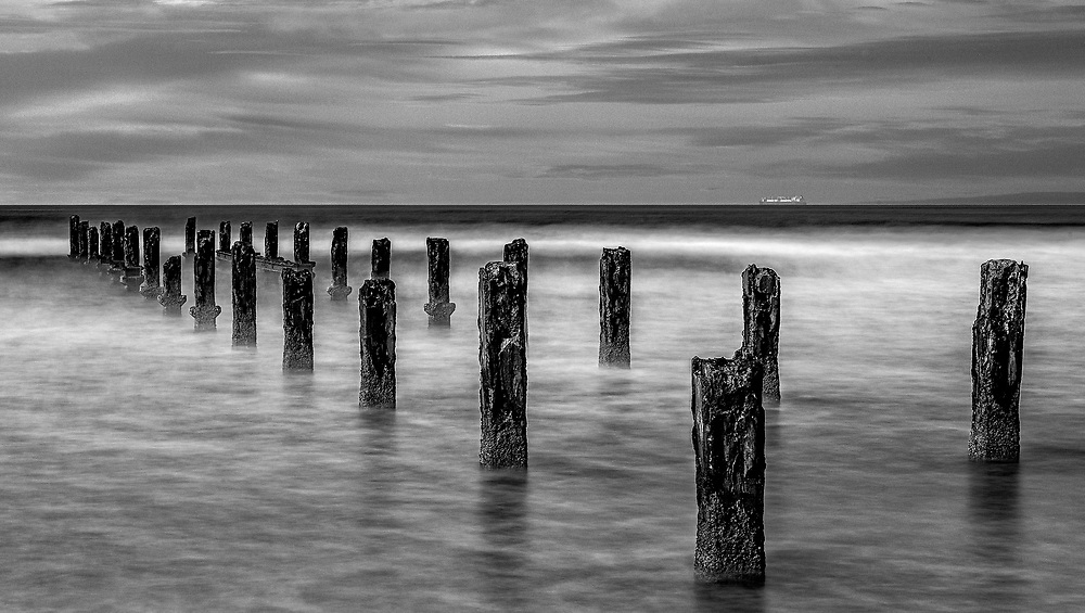 Black and white image with pilings in the sea with a ship at the horizon