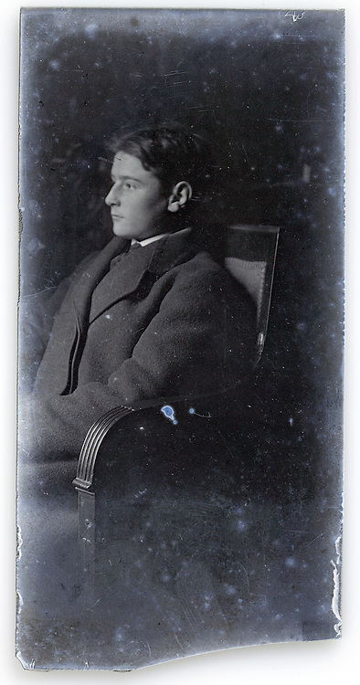 deteriorating glass plate photo of young man sitting for portrait