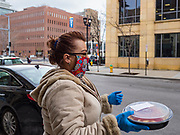 15 APRIL 2020 - DES MOINES, IOWA: CANDICE DEAL carries a free meal to a person waiting in a car at Centro, a restaurant in Des Moines. The owners of Centro handed out 250 pasta meal Wednesday to give back to the hospitality workers in Des Moines. All of the restaurants in Des Moines are closed to sit down service and many that stayed open for take out service have closed as the shutdown has dragged on. Most non-essential businesses in Iowa are closed until 30 April. Because of business closings caused by the Novel Coronavirus (SARS-CoV-2) pandemic, well over 100,000 Iowans filed first time claims for unemployment in the last three weeks, more than applied during the peak of the Great Recession of 2008. Local food banks have seen an unprecedented spike in people seeking nutritional assistance.      PHOTO BY JACK KURTZ