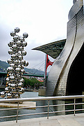The Guggenheim Museum Bilbao is a museum of modern and contemporary art, designed by Canadian-American architect Frank Gehry, and located in Bilbao, Basque Country, Spain. The museum was inaugurated on 18 October 1997 by King Juan Carlos I of Spain. Built alongside the Nervion River, which runs through the city of Bilbao to the Cantabrian Sea, it is one of several museums belonging to the Solomon R. Guggenheim Foundation and features permanent and visiting exhibits of works by Spanish and international artists.