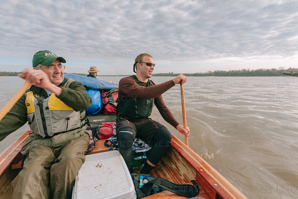 Tim Richardson of the American Land Conservancy (left) and Dave Shively (right) paddle a canoe with John Ruskey (center) in the lower Mississippi River. Canoeing the MIssissippi River. Photo © Robert Zaleski / rzcreative.com<br /> —<br /> To license this image for editorial or commercial use, please contact Robert@rzcreative.com