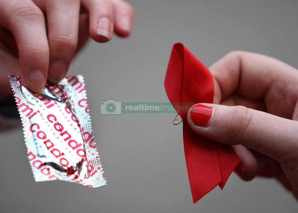 """Red Cross World Aids Day event in Glasgow, where 200 covert campaigners """"freeze"""" in the act of handing each other ribbons and condoms on the Royal Concert Hall steps."""