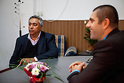 Activist and Roma local councilor Gheorghe Tudor discussing with mayor Manole Aurelian (right) in his office at the town hall in Filipestii de Targ to which Marginenii de Jos belongs. Tudor who has been an activist for social change during the past 25 years, becoming the first elected Roma representative in the local council of Marginenii de Jos in 1992.
