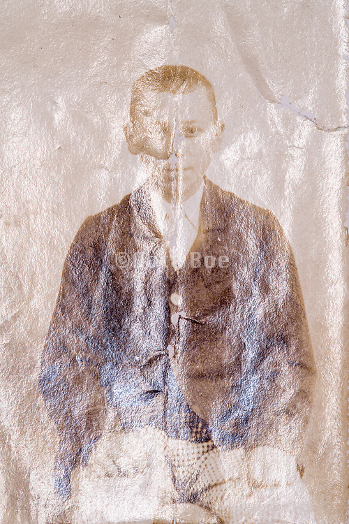 reflected and deteriorating surface photograph with portrait of a young adult boy ca 1900s