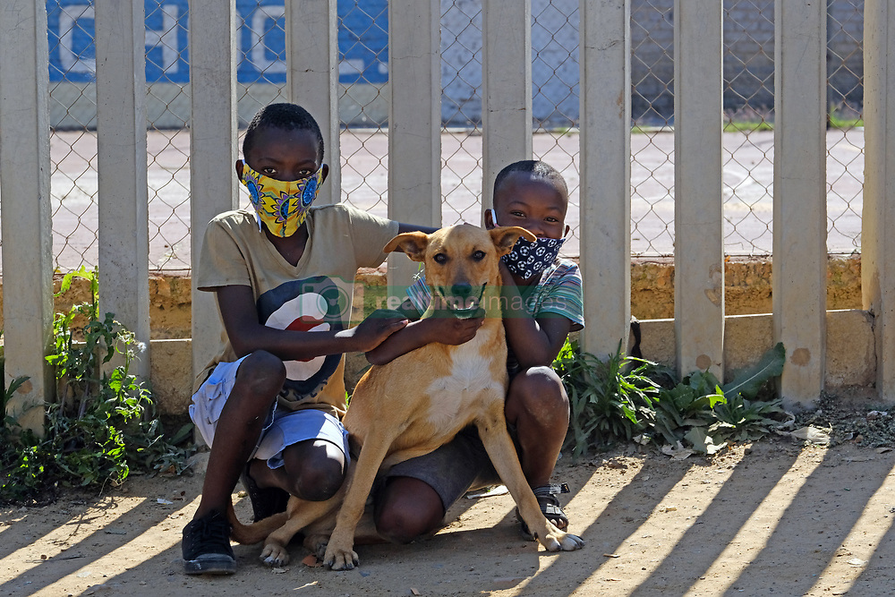 JOHANNESBURG, SOUTH AFRICA - MAY 08: SANDF Young boys with their pet dog near a food distribution centre in Diepsloot on May 08, 2020 in Diepsloot, South Africa. In partnership with with government and Celebration Church, Engen Fuel Retailers contributed food parcels for over 4000 familes in Diepsloot during lockdown level 4. (Photo by Dino Lloyd)