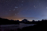 Orion, Taurus and the night sky shine above Oxbow Bend in Grand Teton National Park.