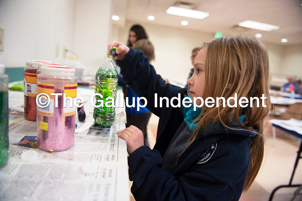 """Leah Masingale puts a few drops of food coloring into a water bottle as part of the children's branch of the Octavia Fellin Public Library's Crafty Kids event Thursday afternoon in Gallup. At the event kids filled a water bottle with water, food coloring and glitter to make a """"genie in a bottle."""""""