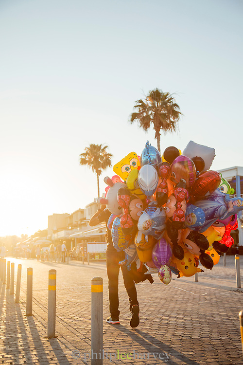 Man walking on sidewalk with bunch of balloons, Paphos, Cyprus