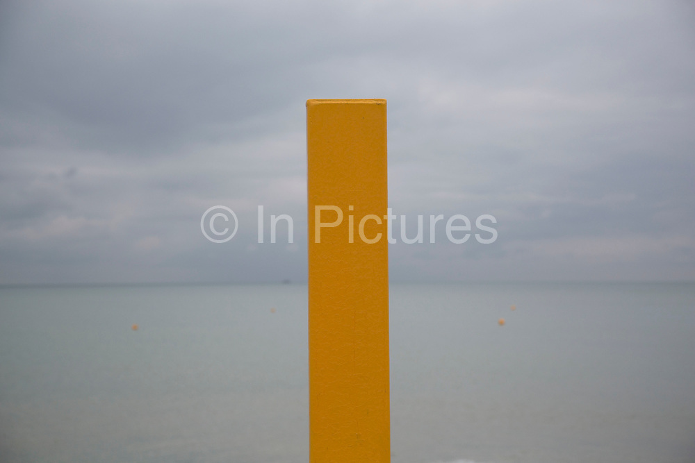 A yellow safety marker looking out to sea from Brighton Beach, Brighton, UK.