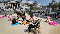 © Licensed to London News Pictures. 12/05/2016. London, UK. Activists from Oxfam, Action Aid and Christian Aid have set up a 'tropical tax haven' in tax avoidance protest in Trafalgar Square. Prime Minister David Cameron is hosting a one day summit which is addressing world corruption. Photo credit: Peter Macdiarmid/LNP