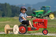 Skagit Valley, WA. farm boy pedaling red toy tractor in field.