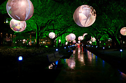 Stock photo of circular globes hanging from the trees lining the walkways